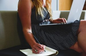Woman holding a laptop and writing in her notebook.