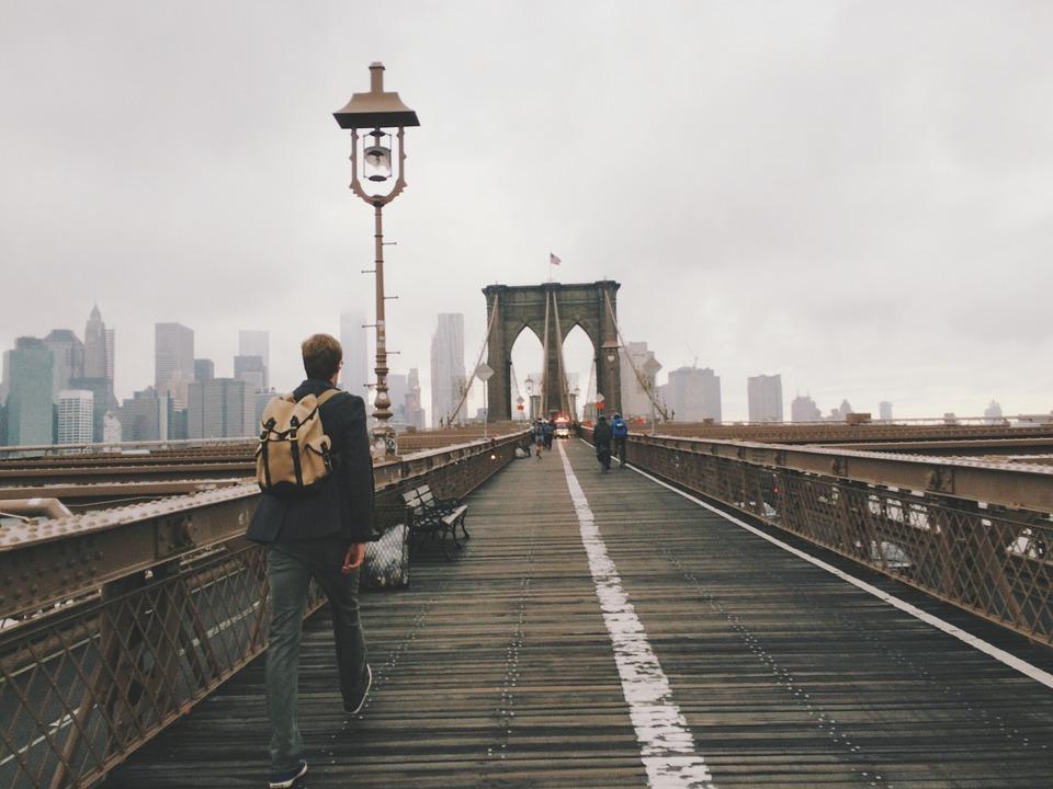 Young man, walking on the Brooklyn bridge.