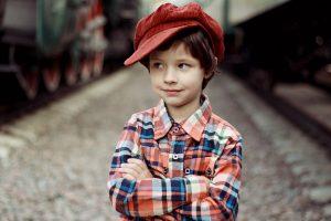 A close up of a boy wearing a cap.