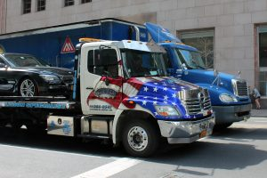 white truck towing black car