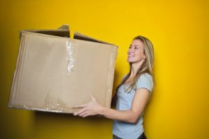 a woman with a box she will use when Moving from Denver to Dallas