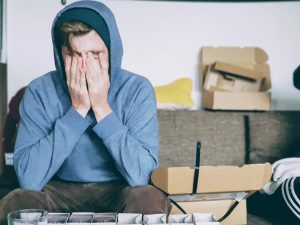 A man holding hands on his face, surrounded with boxes