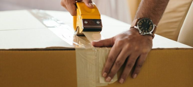 A movers closing a moving box.