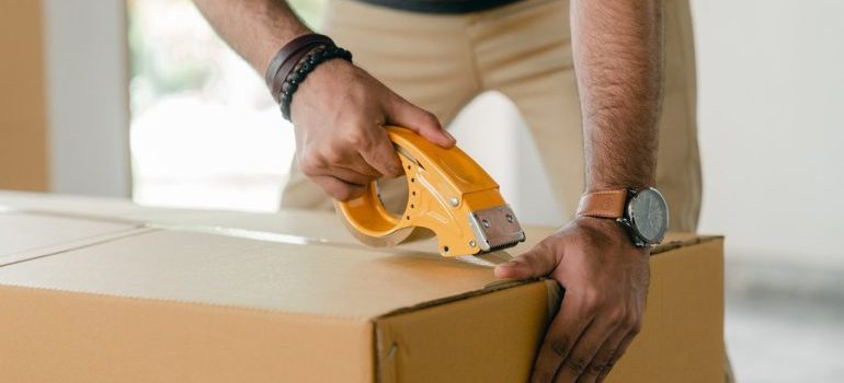 A man taping a cardboard box closed