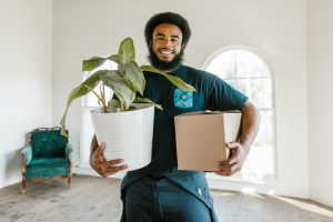 Mover carrying a box and a plant to help you move from Colorado to Florida