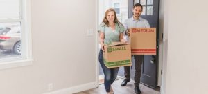 a couple entering a house carrying boxes