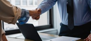 two people shaking hands in an office with a laptop and some notebooks representing finding what is the best moving company