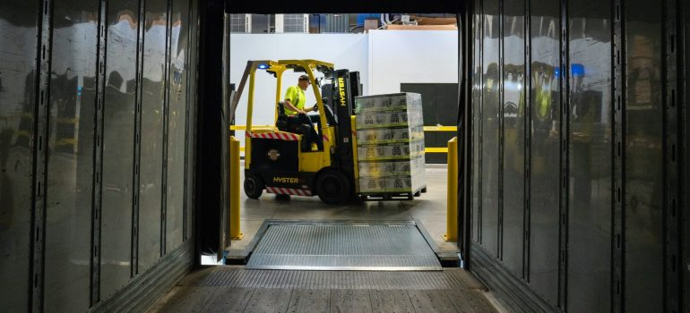 Corridor of the self-storage units and a forklift carrying trucks, you see when you opt for storage facilities.